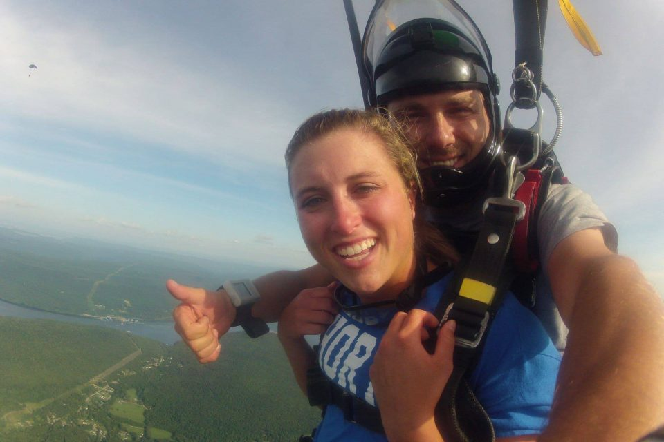Female tandem skydiver wearing blue shirt under canopy