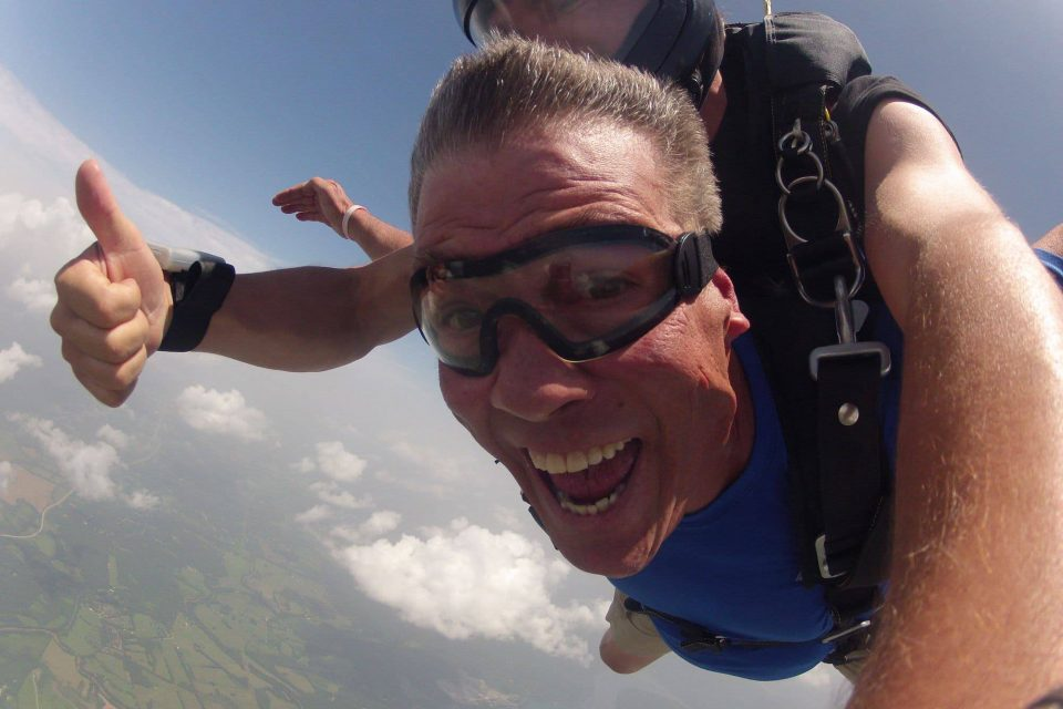 Skydiver enjoying free fall with tandem instructor giving thumbs up