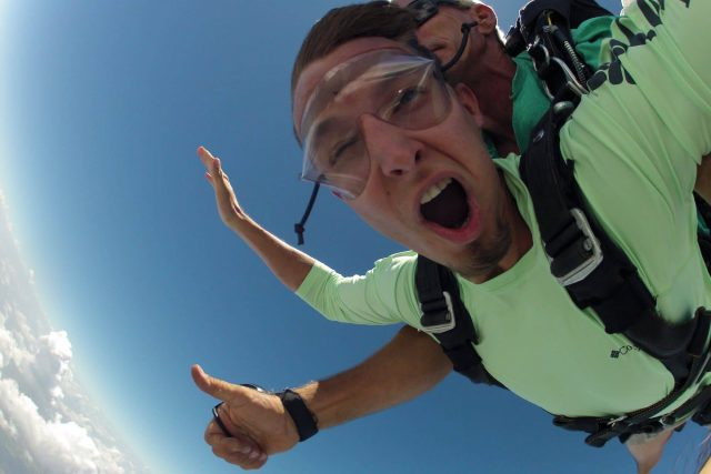 Man in green shirt enjoying free fall with Chattanooga Skydiving Company tandem instructor