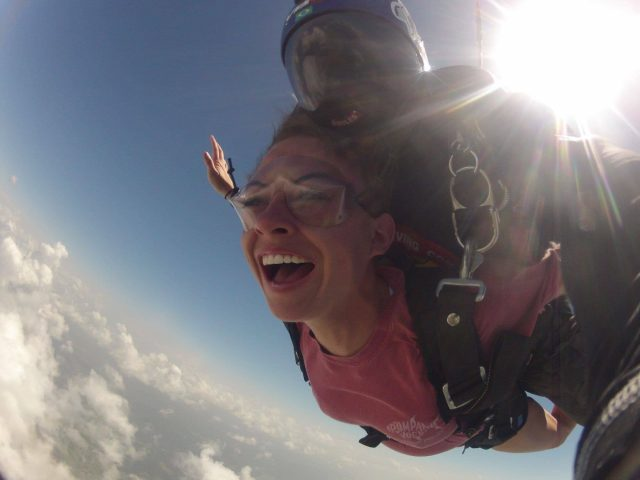 Female tandem skydiver wearing pink shirt smiling during free fall