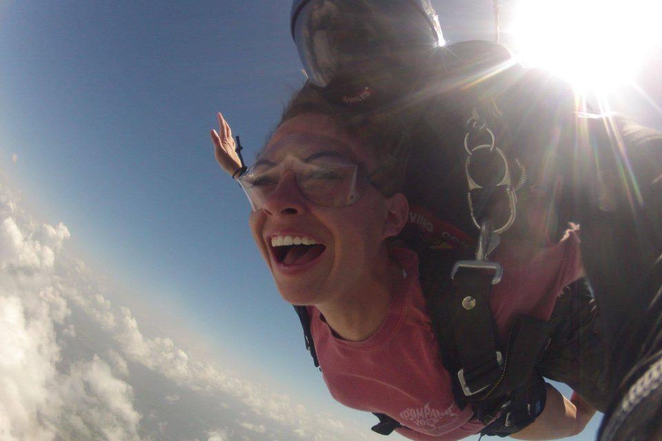 Female tandem skydiver wearing pink shirt smiling during free fall