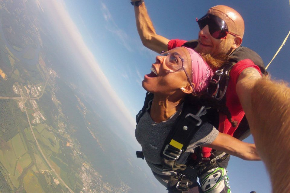 Women wearing pink bandana smiling during free fall