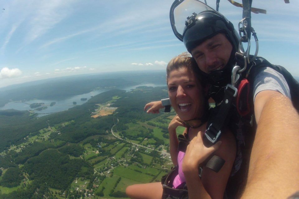 Smiling women wearing pink shirt enjoys the canopy ride down with Chattanooga Skydiving Company tandem instructor