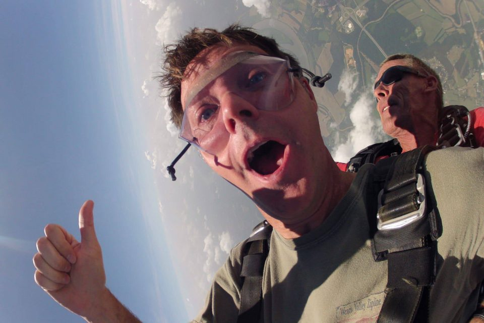 Man in green shirt gives thumbs up during free fall at Chattanooga Skydiving Company