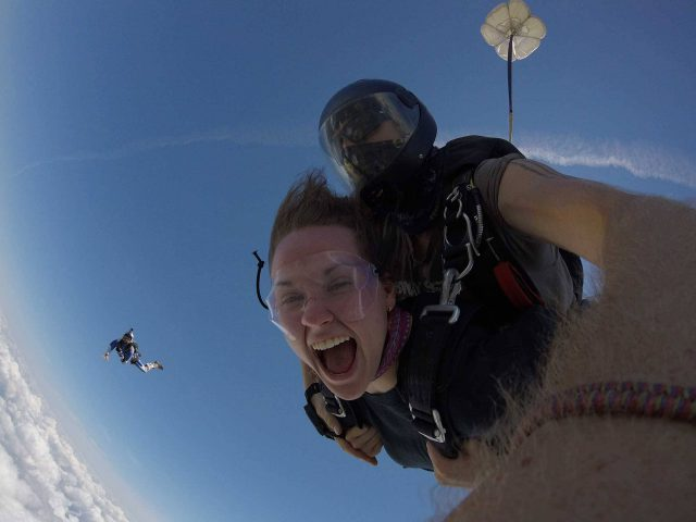 Women enjoys the rush of freefall with tandem instructor