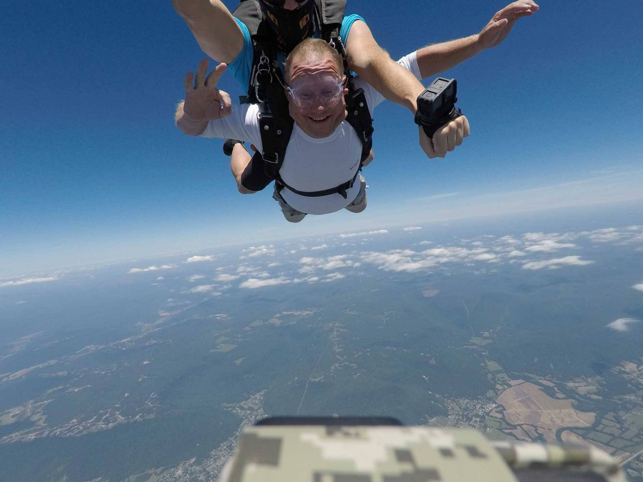 Man wearing white shirt holds his arm out in joy during free fall