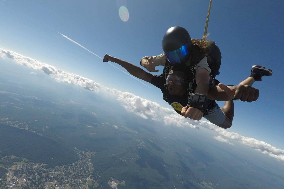 Male tandem skydiver gives thumbs up during free fall at Chattanooga Skydiving Company