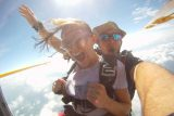 Women smiles while jumping into free fall with tandem instructor
