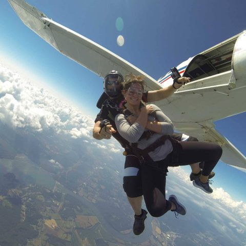 Female wearing gray shirt takes the jump out of the Chattanooga Skydiving Company aircraft