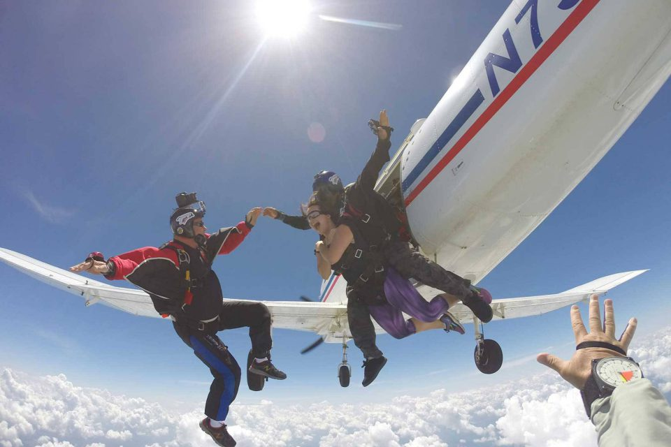 Women wearing purple plants smiles after jumping from the Chattanooga Skydiving Company airplane and into free fall
