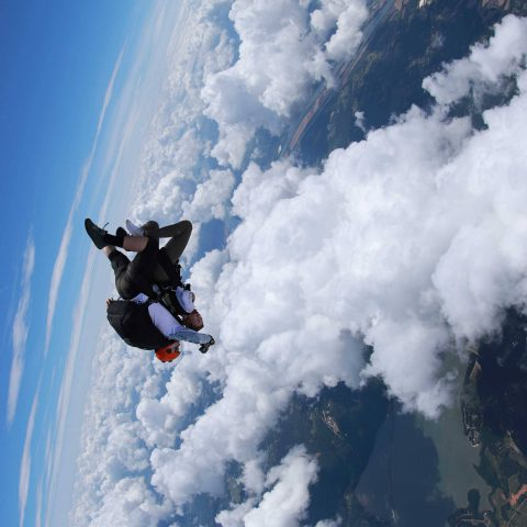 Tandem skydiver enjoying free fall surrounded by white clouds and blue skies