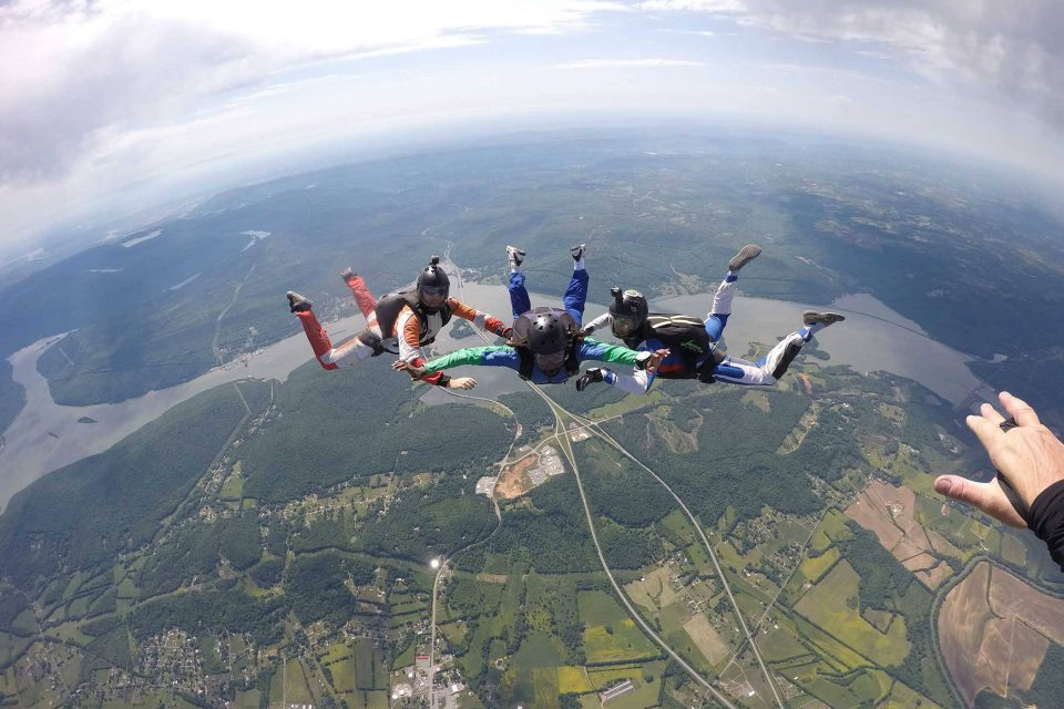 AFF instructors guide student on free fall position during a skydive