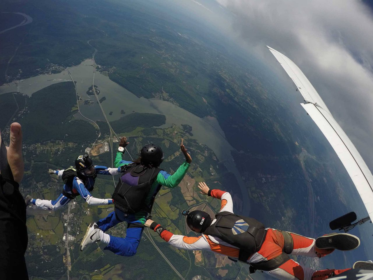 AFF student wearing green and blue skydiving gear while in free fall