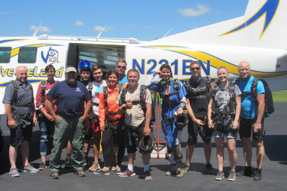 Chattanooga Skydiving Company staff stand in front of aircraft wearing skydiving gear